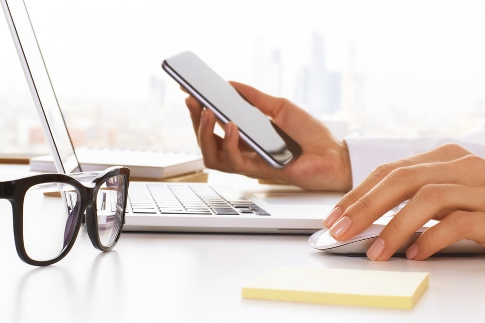 Closeup,Of,Business,Woman,Hands,Using,Cell,Phone,And,Laptop